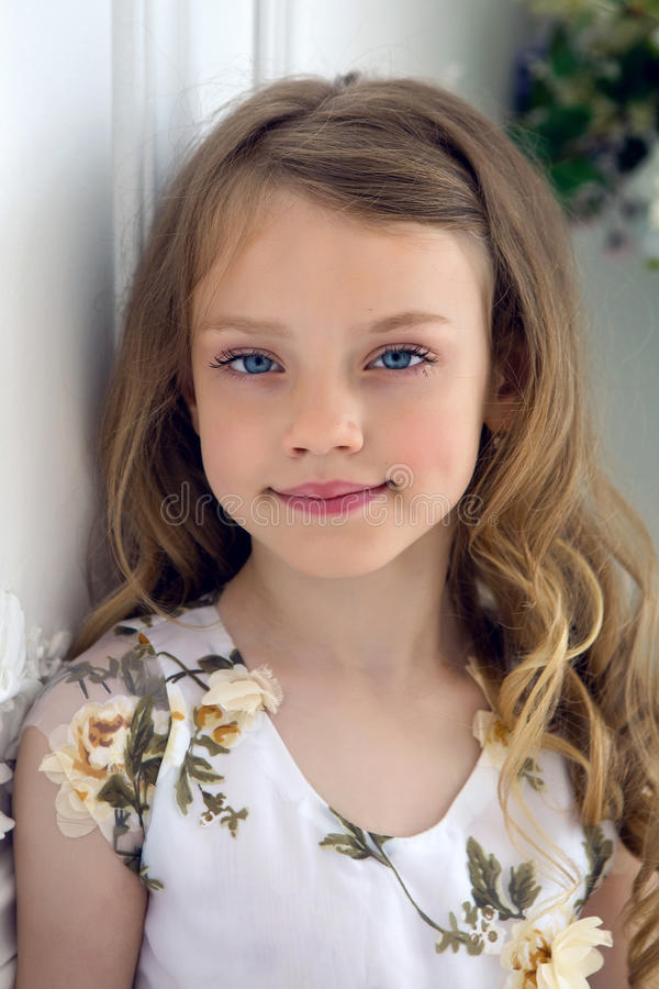 Portrait of a girl seven years old with blond hair and white dress royalty free stock photography