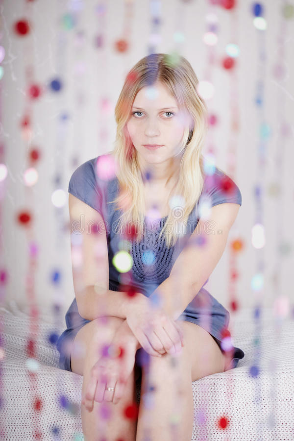 Portrait Of Girl That Sits Behind Curtain Royalty Free Stock Photography