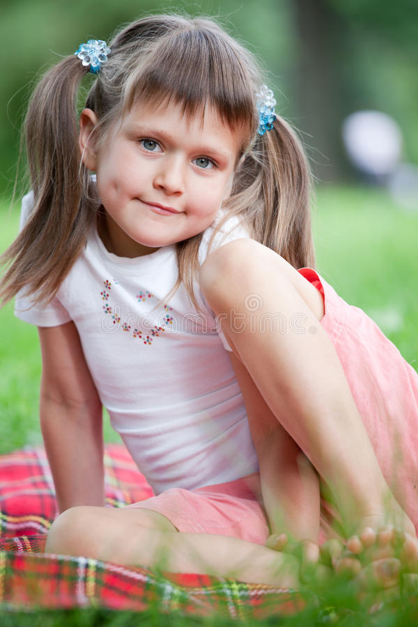 Portrait of girl sitting on plaid, grass in park stock photography