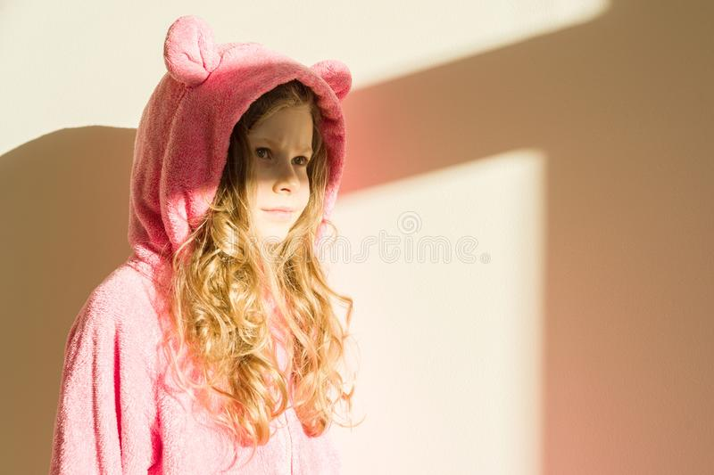 Portrait of a girl in soft warm pink pajamas. Girl 7 years old, blonde with long curly hair, in a hood, looking away. Background l stock image