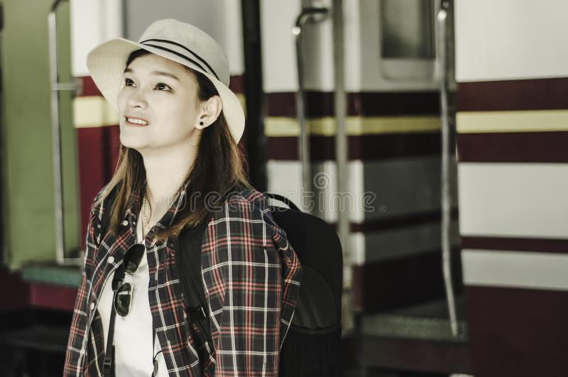 Portrait girl standing waiting for train,in train station, to plan a trip, background of train is parked in station, Travel royalty free stock image
