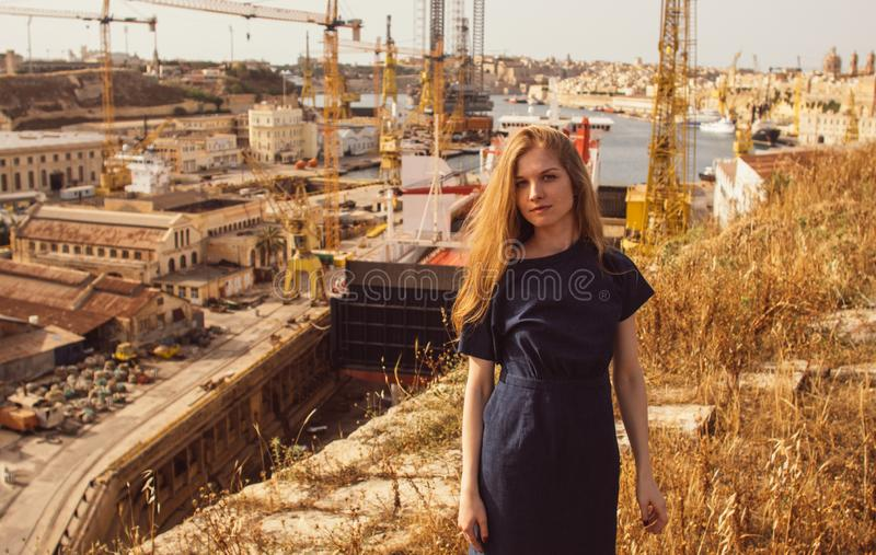 Portrait of girl on the sun, cranes and docks on the background stock photo