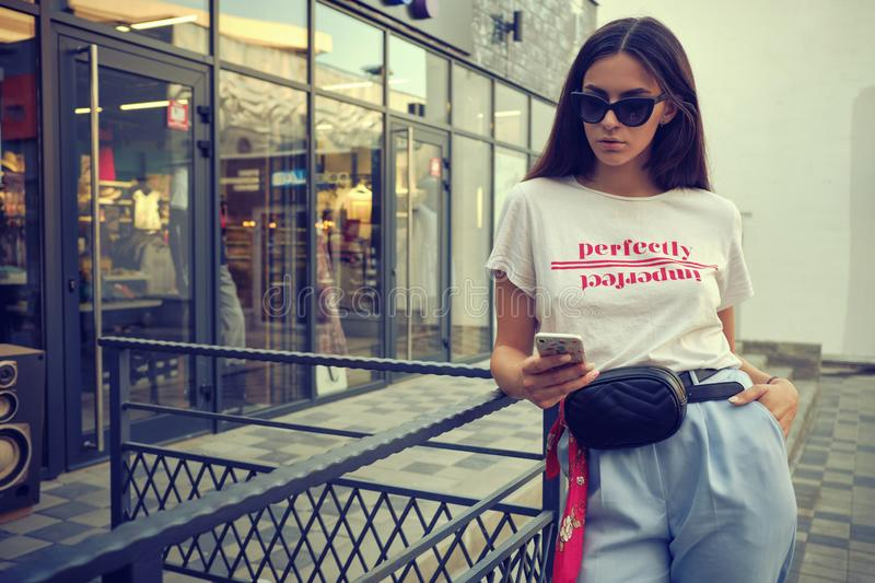 Portrait of a girl in sunglasses posing near a city mall, using smartphone. Dressed in white t-shirt, blue trousers. Close-up portrait of a beautiful young stock image