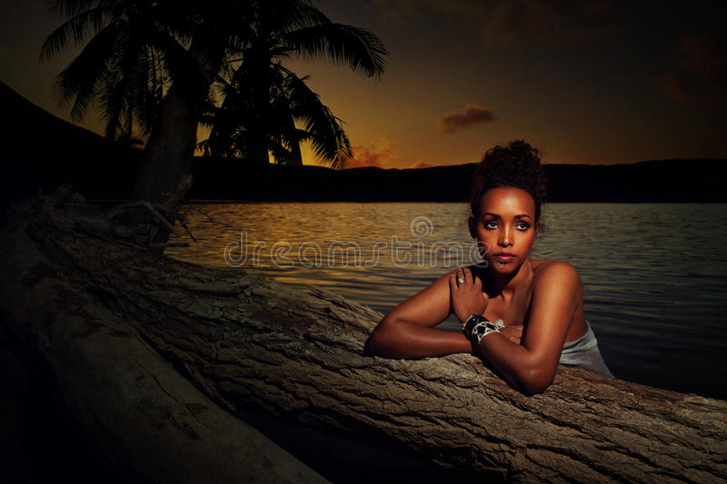 Portrait of a girl at sunset. Mystical portrait of a beautiful young girl at sunset leaning on the trunk of a palm tree with an ocean backdrop and soft shadowed stock photos