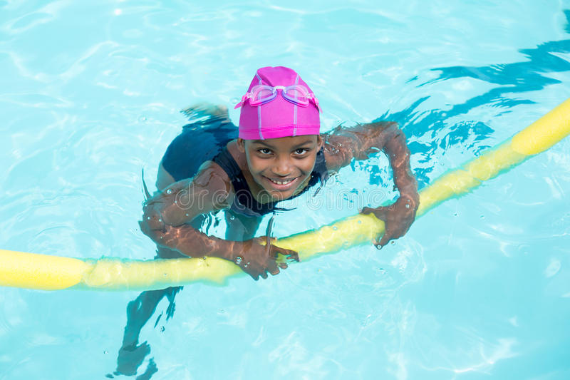 Portrait of girl swimming with pool noodle royalty free stock image