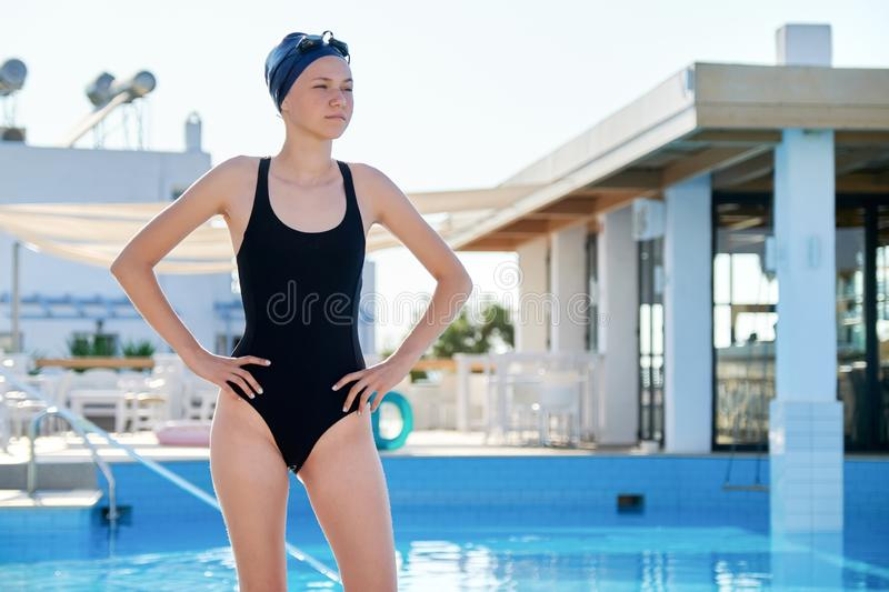 Portrait of girl in swimsuit with goggles swimming cap, outdoor pool stock photography