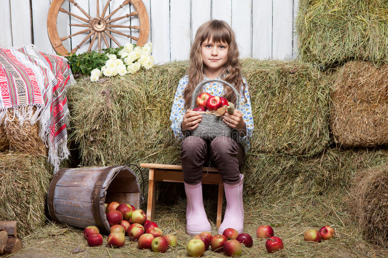 Portrait of girl villager with basket of apples. Portrait of friendly little blond girl villager sitting on stool with basket of apples in hands near inverted stock photo