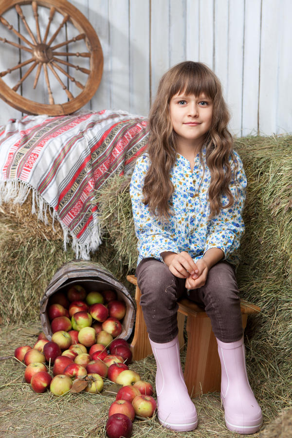Portrait of girl villager near pail with apples. Portrait of friendly little blond girl villager sitting on stool near inverted pail with apples in wooden royalty free stock image