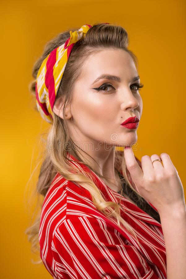 Portrait of a girl in vintage style. Lips with red lipstick. Bandana in the hair.Classic soft focus stock photography