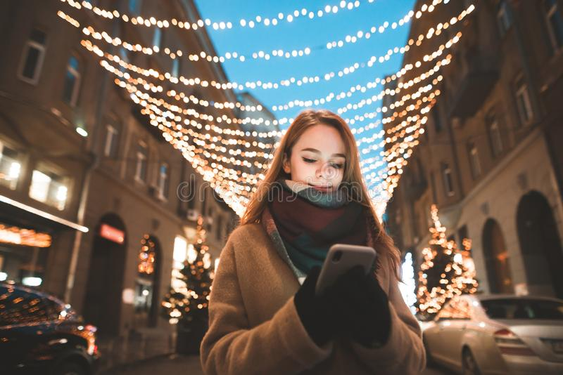 Portrait of a girl in warm clothes standing outdoors against a background of bokeh lights and use a smartphone stock photography