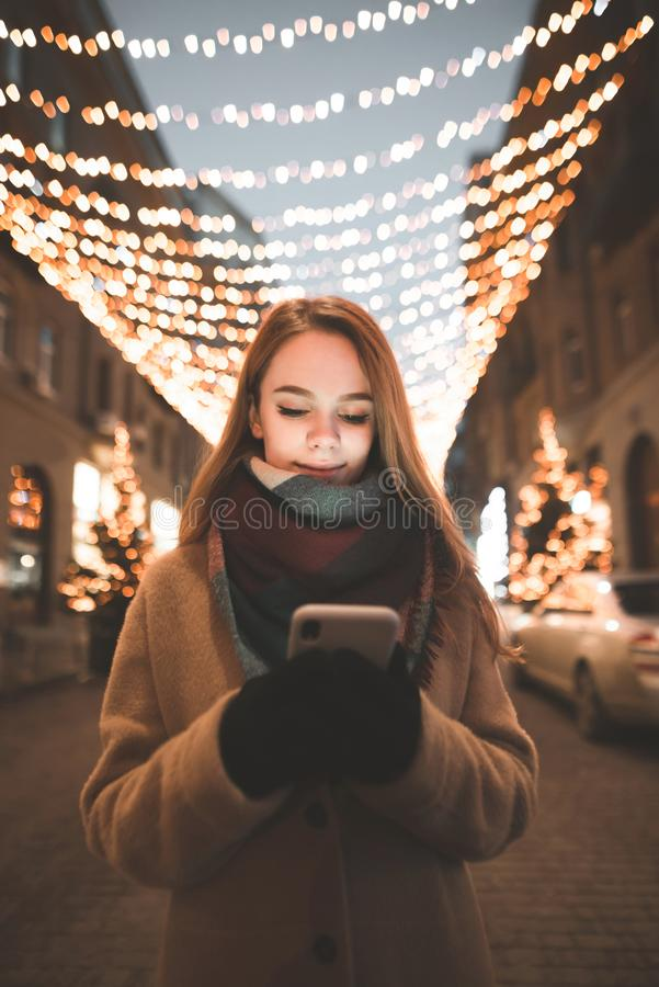 Portrait of a girl in warm clothes standing outdoors against a background of bokeh lights and use a smartphone stock image