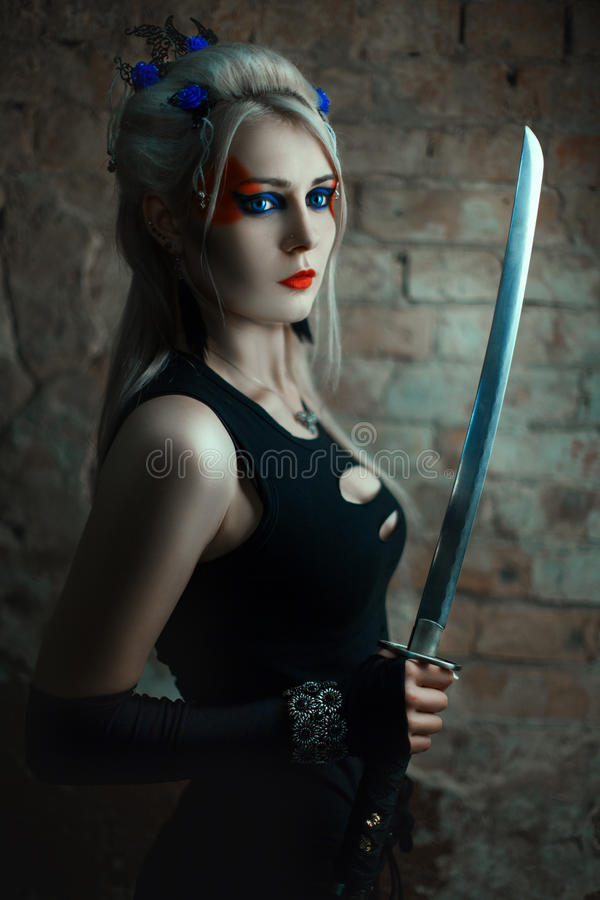Portrait of a girl warrior with sword. Portrait of a girl warrior with a sword. She is in a dark room stock image