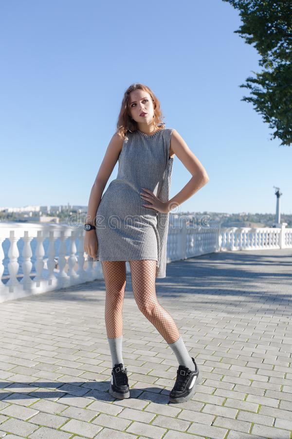 Portrait of girl on waterfront. Attractive female person in gray short sleeveless dress posing with feet inwards on paving slab royalty free stock photography