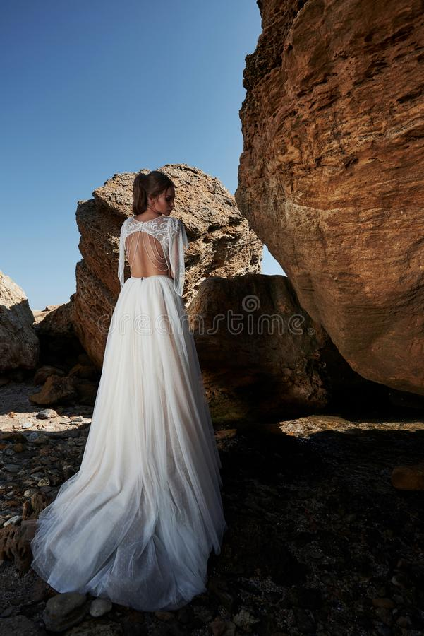 Portrait of a girl in a wedding gorgeous dress posing a photographer on the beach. The bride is on the rocks stock photo