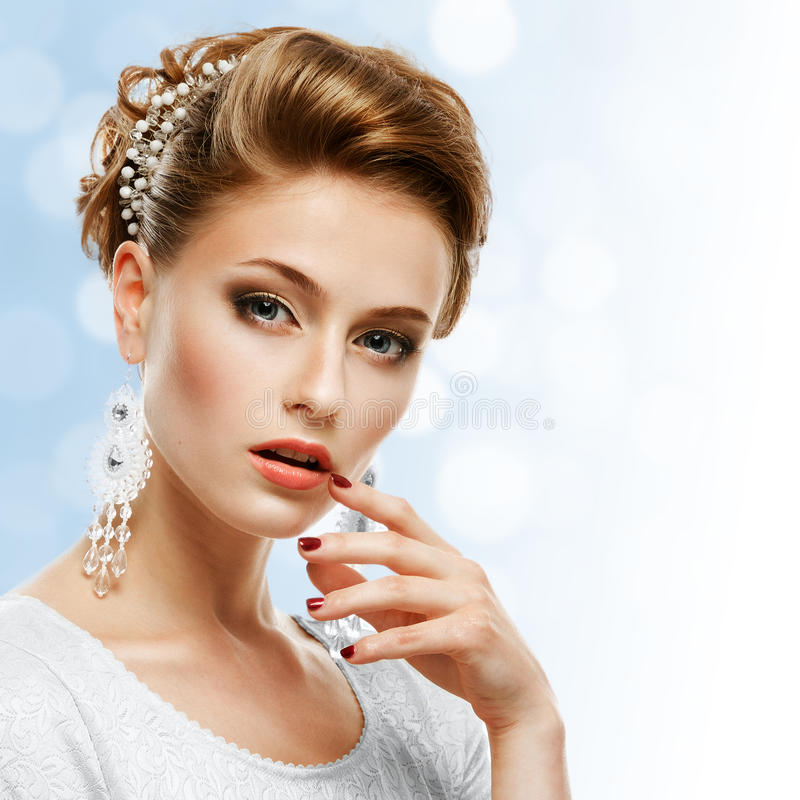 Portrait of a girl in a white dress and jewelery on a blue background. stock images