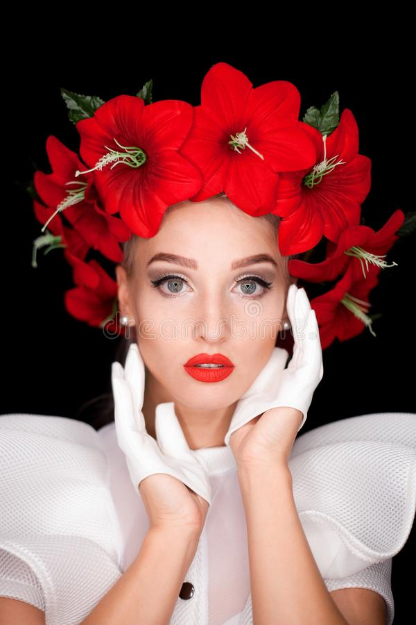 Portrait of a girl in white with a wreath of red flowers on her head, stock image