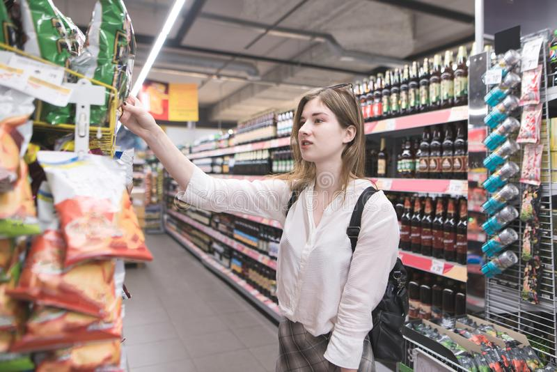 Portrait of a girl who buys chips in a supermarket. Woman chooses and buys the products in the store stock image