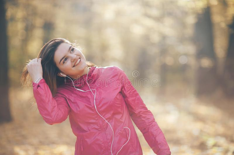 Portrait of a girl who trains and listens to music. Good morning light royalty free stock images