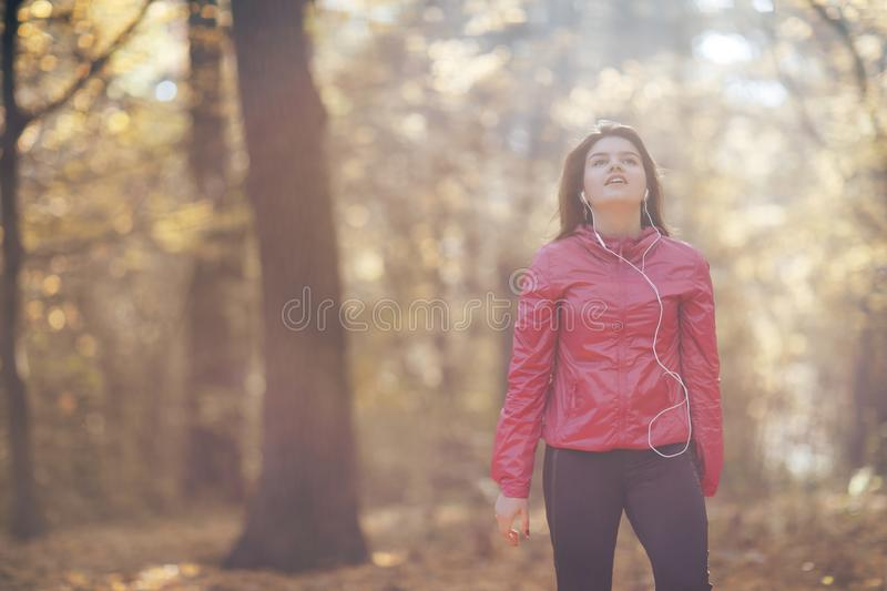 Portrait of a girl who trains and listens to music in the morning autumn park stock photo