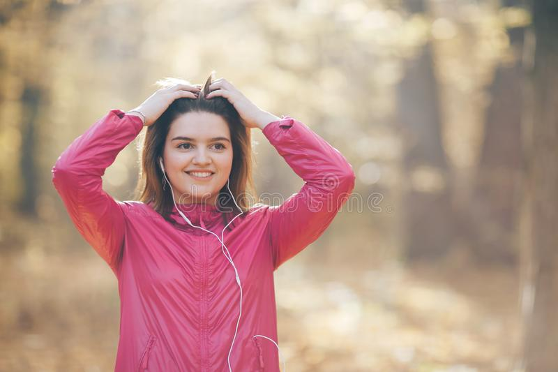 Portrait of a girl who trains and listens to music in headphones stock photo