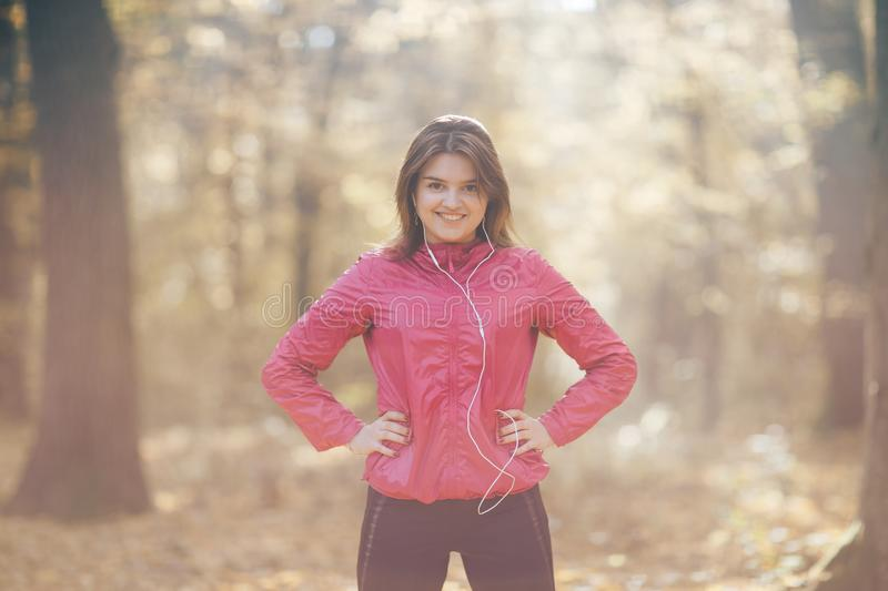 Portrait of a girl who trains and listens to music in the morning autumn park royalty free stock images
