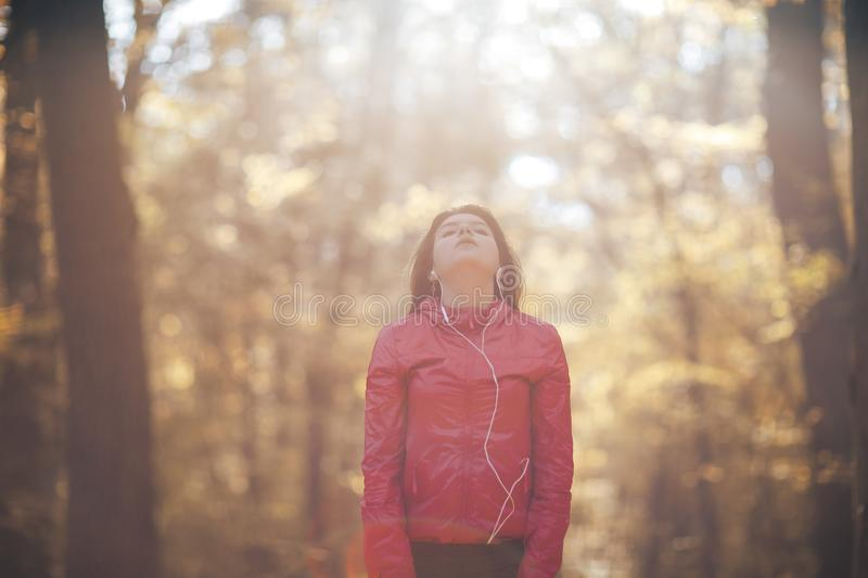 Portrait of a girl who trains and listens to music in the morning autumn park stock photos
