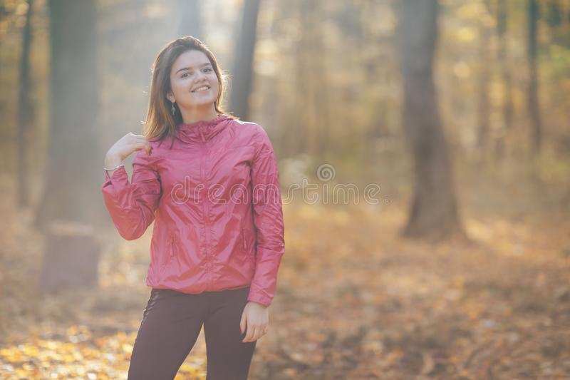 Portrait of a girl who trains in the morning autumn park. Good morning light royalty free stock image