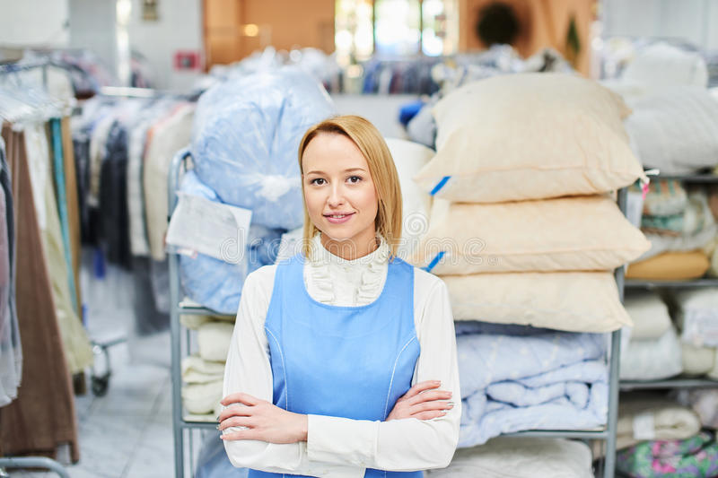Portrait of a girl worker in a warehouse Laundry with clean clothes. At the dry cleaners stock images