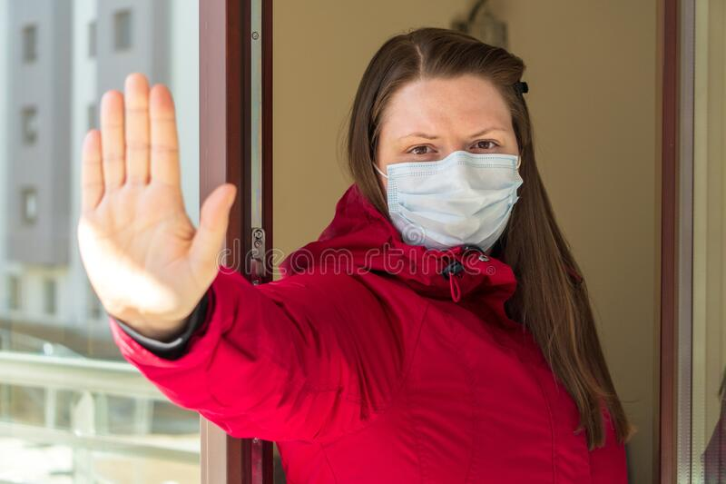 Portrait of a girl or young woman in a medical mask being quarantined at home during the coronavirus pandemic. Self-isolation,. Girl or young woman in a medical royalty free stock photography
