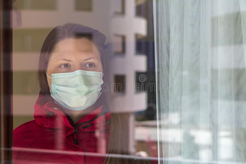 Portrait of a girl or young woman in a medical mask being quarantined at home during the coronavirus pandemic. Self-isolation,. Girl or young woman in a medical stock photos