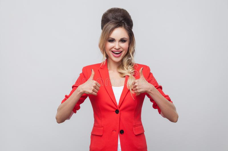 Portrait of glad beautiful business lady with hairstyle and makeup in red fancy blazer, standing, thumbs up and looking at camera. With thumbs up. indoor studio royalty free stock photo