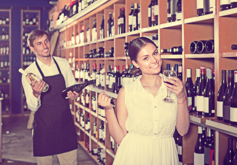 Portrait of glad female customer tasting wine before purchasing royalty free stock photo