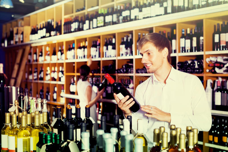 Portrait of glad male customer taking bottle of wine in store stock images