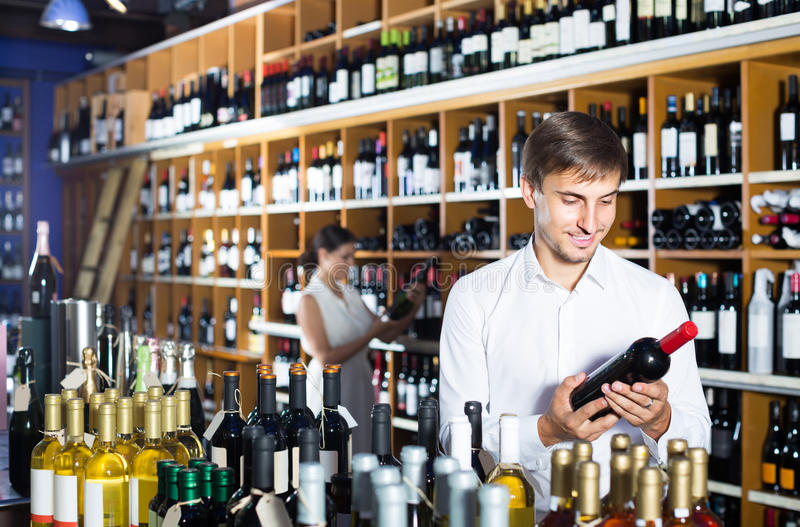 Portrait of glad male customer taking bottle of wine in store royalty free stock photos