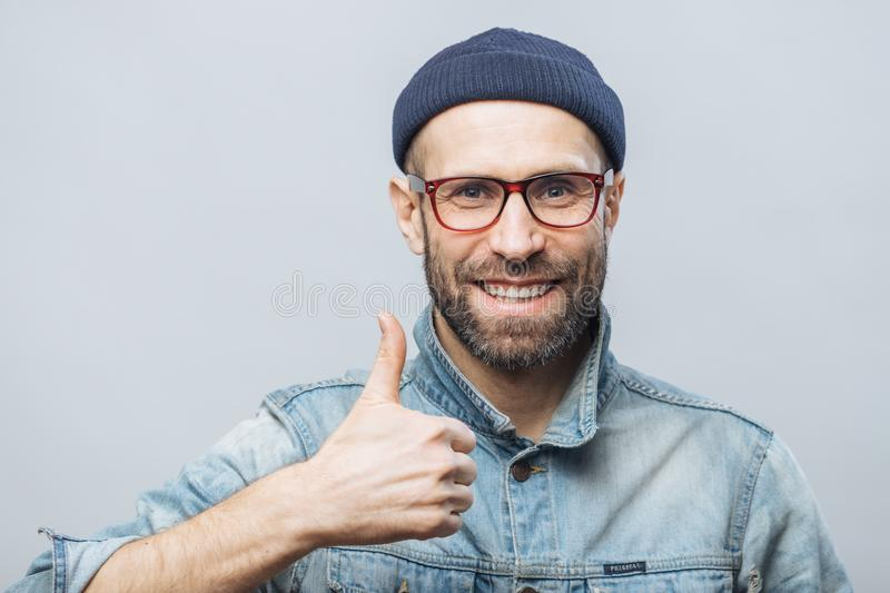 Portrait of glad middle aged male witth thick beard and mustache shows his satisfaction with something, raises thumb, has positive royalty free stock photo