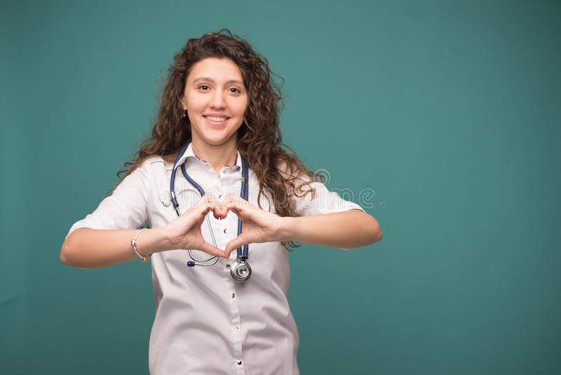 Portrait of glad smiling doctor in white uniform standing shows heart on green background . copy space stock photo