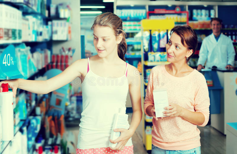 Portrait of glad woman with daughter teenager. Portrait of happy women with daughter teenager shopping healthcare products in drug store stock image