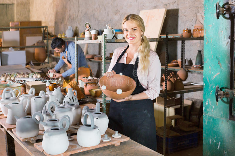 Portrait of glad woman pottery worker with ceramic crockery. Portrait of cheerful efficient women pottery worker with ceramic crockery in hands in studio royalty free stock image