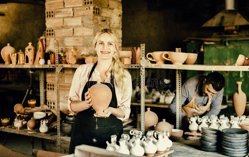 Portrait of glad woman pottery worker with ceramic crockery. Portrait of pleasant efficient women pottery worker with ceramic crockery in hands in studio royalty free stock photo