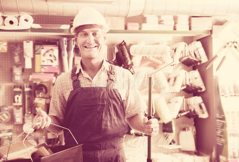 Portrait of glad workman choosing soft roller royalty free stock photography