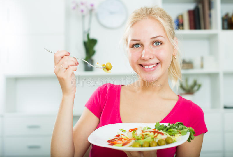 Portrait of glad young blond girl eating salad stock image