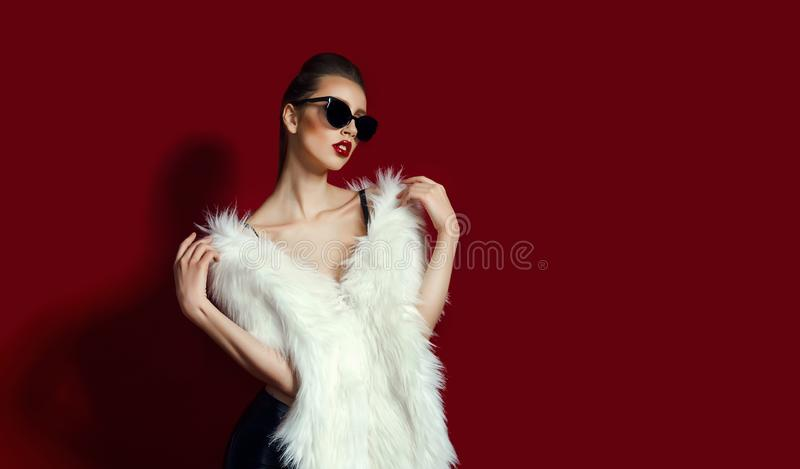 Portrait of glam girl in white fur on red background. Fashion photo stock images