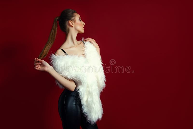 Portrait of glam girl in white fur on red background. Fashion photo stock photography