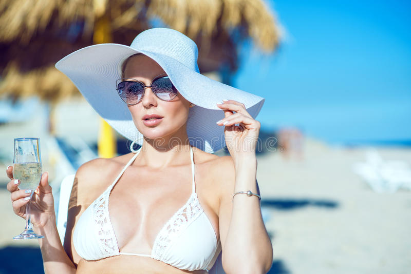 Portrait of glam lady in white swimming bra, wide-brimmed hat and sunglasses sitting on the chaise longue with a glass of stock photos