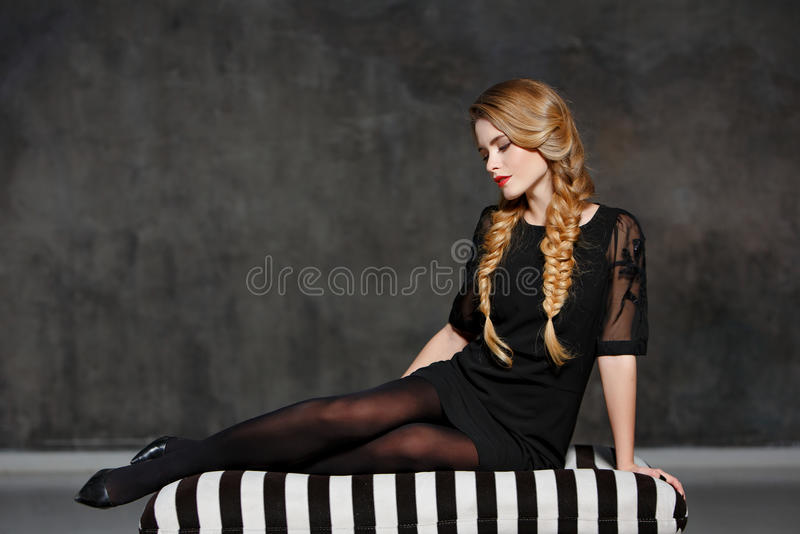 Portrait of a glamorous beautiful girl with pigtails and bright. Makeup sitting on a striped couch in a black dress in the studio, close-up royalty free stock image