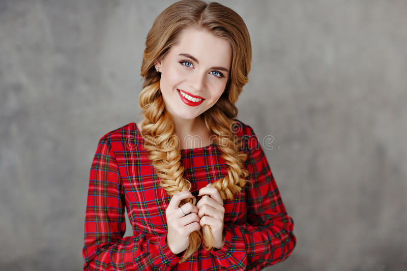 Portrait of a glamorous beautiful smiling girl with bright makeup in a red plaid dress and pigtails, in the studio on a gray back royalty free stock images