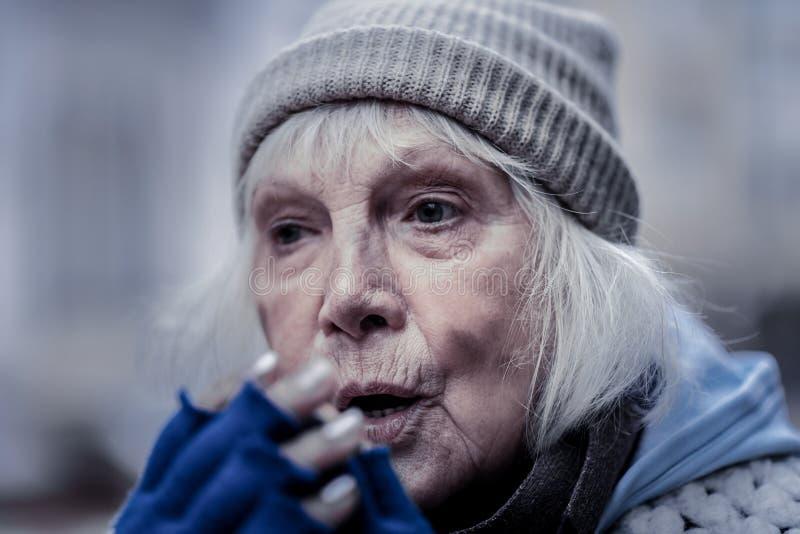 Portrait of a gloomy poor elderly woman stock photography