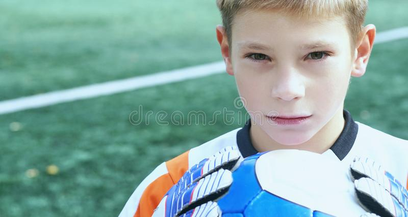 Portrait of teenage goal keeper holding ball on school soccer pitch royalty free stock images