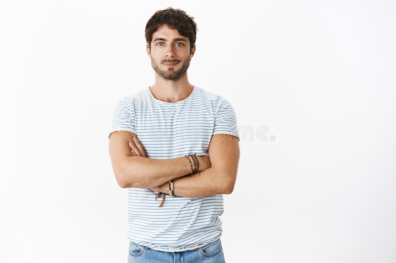 Portrait of good-looking confident and enthusiastic young masuline male fitness instructor holding hands crossed over royalty free stock image