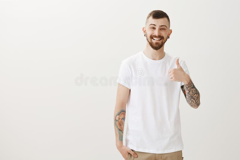 Portrait of good-looking happy male student with beard and tattoos, showing thumbs up and smiling cheerfully, giving royalty free stock image